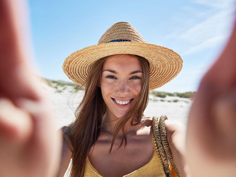 a364c9d8c صورة لامرأة مبتسمة ترتدي قبعة عند الشاطئ