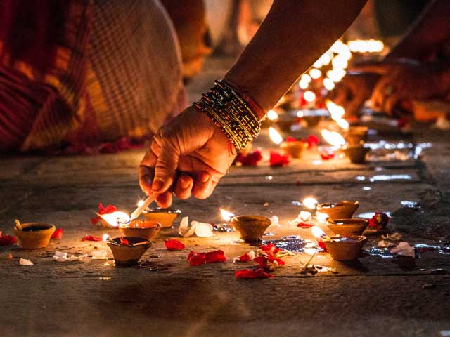 A hand holding illuminated candles on Diwali